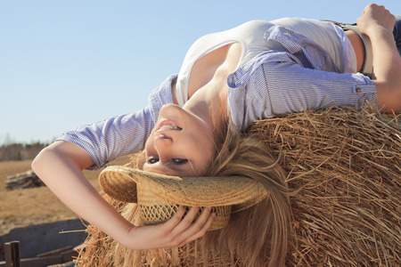 cowgirl hat: Young american cowgirl woman portrait outdoors.