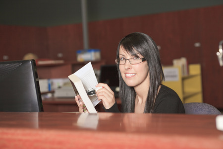 librarian: A Smiling female librarian holding a book standing behind the desk looking at camera