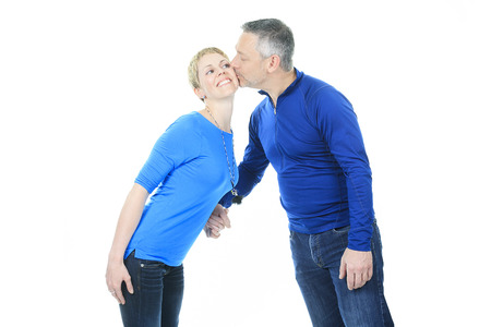 A Thoughtful couple giving kiss on white background. Imagens