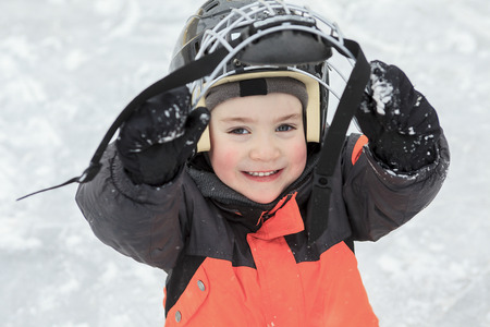 outside: A portrait of happy child in winter with a hcokey helmet