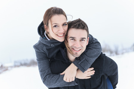 looking towards camera: A Young Couple outside in the winter season Stock Photo