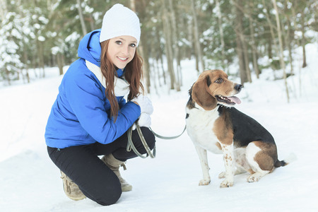 A Portrait of a pretty young woman with her pet dog in winter season.