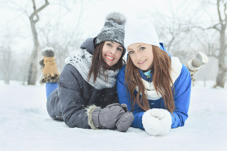 winter woman: Two happy young girls lay on the snow having fun in winter park Stock Photo
