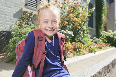 kindergartener: A Happy little girl outside with backpack Stock Photo