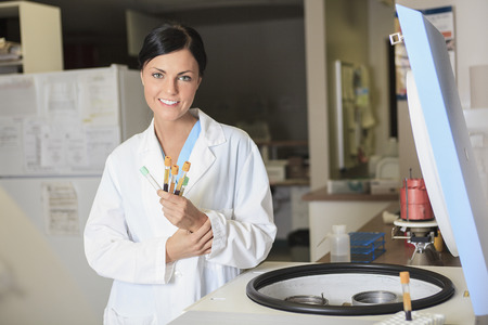A scientist at work in a laboratory puting some thing on a machine. Stock Photo