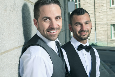 gay male: A Portrait of a loving gay male couple on their wedding day with sky on the back.