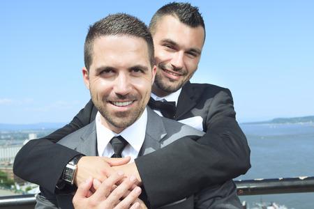 Een portret van een liefdevolle homoseksuele man paar op hun trouwdag met de hemel op de rug. Stockfoto