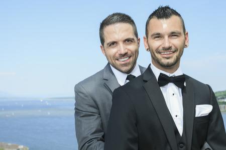 amor gay: Un retrato de una pareja de hombres gay amoroso día de su boda con el cielo en la parte posterior.
