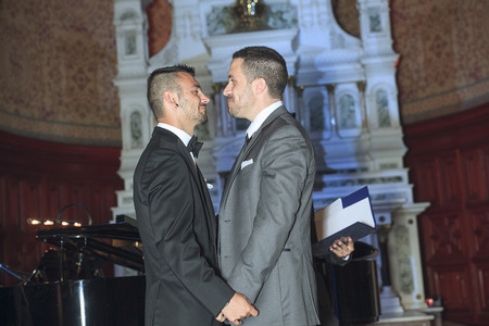 gay male: A Portrait of a loving gay male couple on their wedding day inside the church. Stock Photo