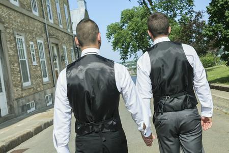 Um retrato de um casal gay masculino amoroso no dia do casamento. A foto é taked na rua da cidade de Quebec.