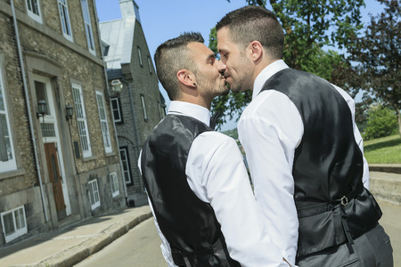 A Portrait of a loving gay male couple on their wedding day. The photo is taked on the Quebec city street. Stock Photo