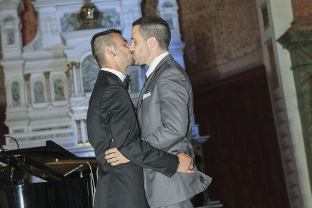 A Portrait of a loving gay male couple on their wedding day inside the church. Stock Photo