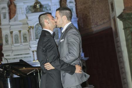 gay men: Un retrato de una pareja de hombres gay amorosa en su día de la boda dentro de la iglesia. Foto de archivo