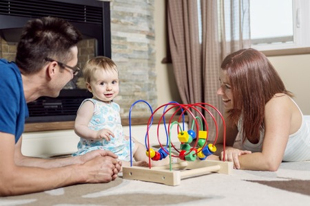 A parents baby sitting on floor play with toy