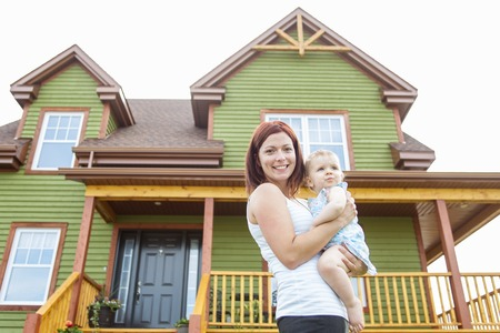 hispanic kids: A Mother and baby in front of the house Stock Photo