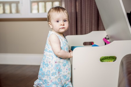 toy box: A small beautiful baby girl on the front of his toy box Stock Photo