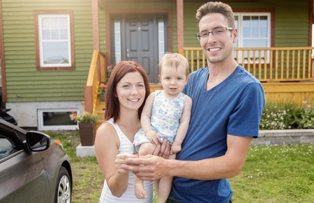 front of: A Portrait of couple with their adorable daughter in front of house