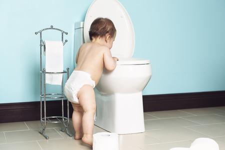 papel de baño: Un niño en el cuarto de baño mira el aseo Foto de archivo