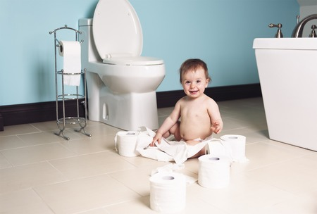 playful behaviour: A Toddler ripping up with toilet paper in bathroom