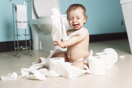 restroom: A Toddler ripping up with toilet paper in bathroom