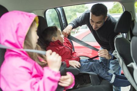 cinturon seguridad: Un padre preocupado por la seguridad de sus hijos en un coche