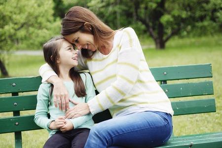 familias felices: Una madre y su hija en el bosque en un prado