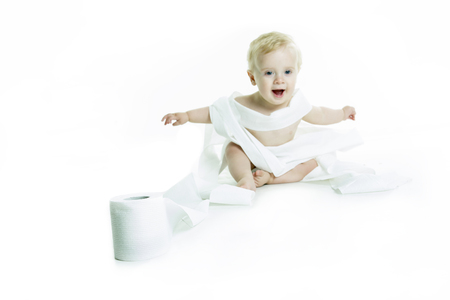 playful behaviour: A Toddler ripping up toilet paper in bathroom studio