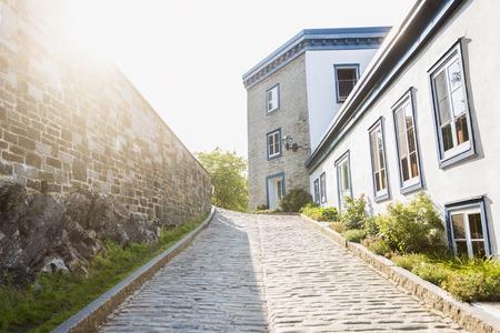 Een straat van de oude stad van Quebec met zon aan de linkerkant