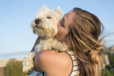 kiss: A portrait of beautiful girl keeping pretty white West Highland dog outdoor Stock Photo