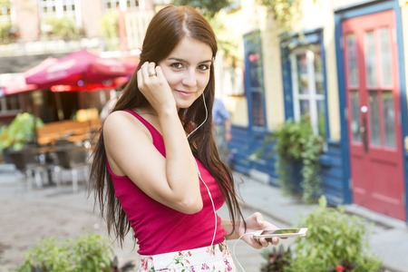 earphone: A Young happy teenage girl in urban place