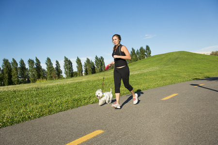 1 person: A Beautiful young woman jogging with her dog Stock Photo