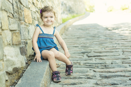 4 5 year old: A Little girl in an urban setting smiles at the camera.