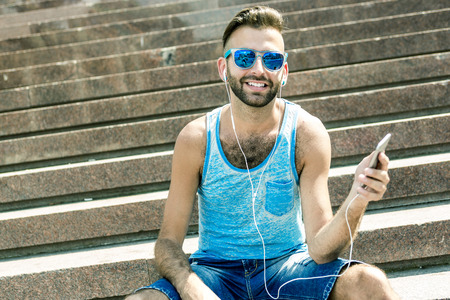earbuds: A Man listening to the music with earbuds from a smart phone