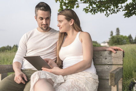 happy family nature: A Young couple in love outdoor at the sunset with a tablet