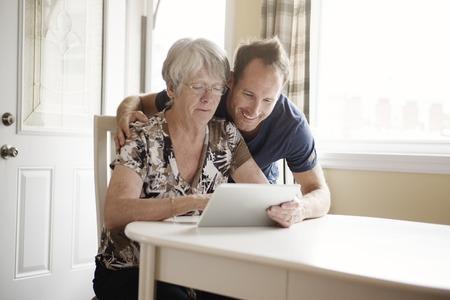 キッチンでは、タブレット コンピューターを保持している年配の女性