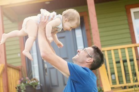 Een vader en dochter spelen in de voorkant van het huis