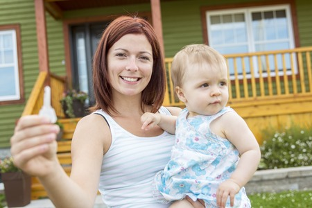 house property: A Mother and baby in front of the house Stock Photo