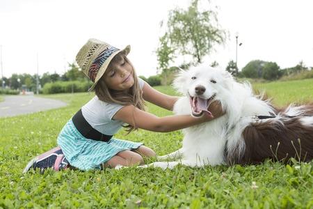 kinder spielen: Ein Porträt von Mädchen halten hübschen Hund im Freien Lizenzfreie Bilder