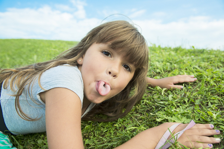 girl tongue: Beautiful portrait of a little girl outside on grass