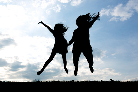 black and pink: Silhouette of a young mother and daughter having fun on backlit Stock Photo