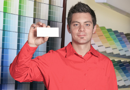 empleados trabajando: Un empleado de una ferretería en el trabajo que sostiene una tarjeta blanca.