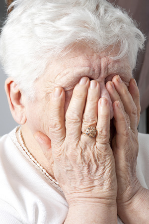 congenial: A portrait of an elderly woman having some depress problem. She have the hand on si face.