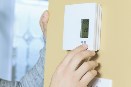 A man set the thermostat at house.