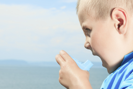 A young boy having a asthma problem using inhaler outside