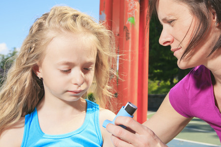 asthmatic: A mother using inhaler with her asthmatic daughter. Stock Photo