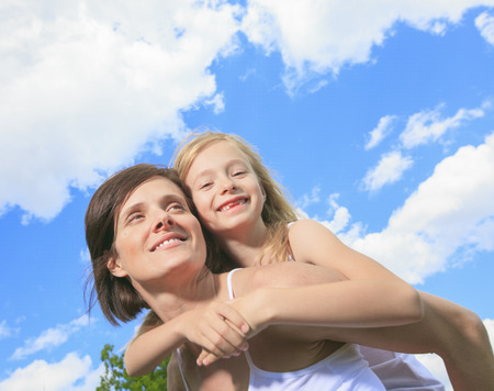 8 year old girl: A Mother Giving Her Daughter A Piggy Back Ride Stock Photo