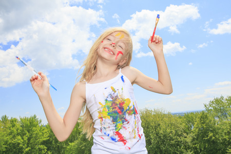 children painting: A little blond girl with paint on the face