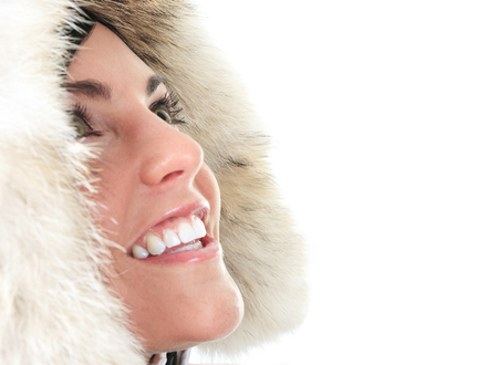 skin care: A portrait of a beautiful young woman with a winter coat in studio.