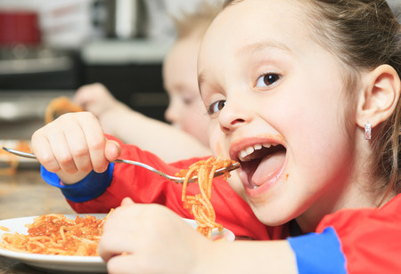 A Little girl eat pasta in the kitchen table