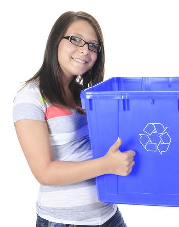niños reciclando: Una mujer joven que lleva un recipiente de plástico lleno de vacío domésticos reciclables. Reciclaje de concepto Foto de archivo
